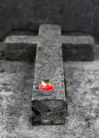 memorial cross: Lápida en forma de cruz viejo con poca vela encendida