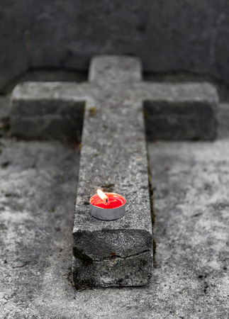 memorial candle: Old cross shaped tombstone with little burning candle