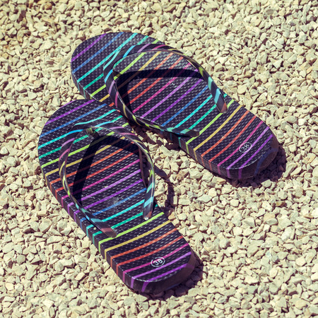 flipflops: Pair of flip-flops on stony beach. Picture with colorized retro look