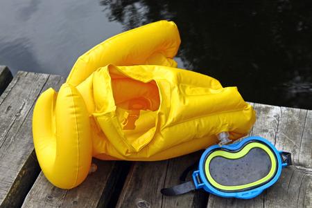 lifejacket: Yellow life jacket and diving mask for children on lake bridge