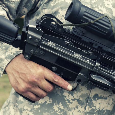 finger on trigger: Colorized picture of soldier holding his finger on trigger of automatic gun