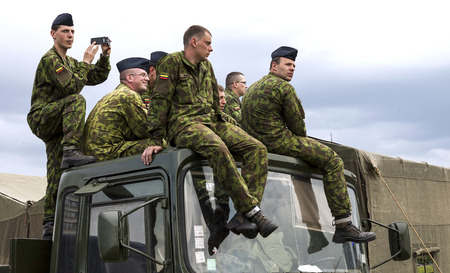 lithuanian: VILNIUS, LITHUANIA - MAY 17, 2014: Lithuanian army soldiers sitting on the top of military truck during Public and Military Day Festival in Vilnius, Lithuania Editorial