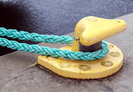 mooring: Horizontally oriented picture of port pier with yellow mooring bollard and green ropes Stock Photo