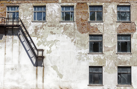 abandoned house window: Grunge architecture details. Old abandoned factory with metal staircase and broken windows Stock Photo