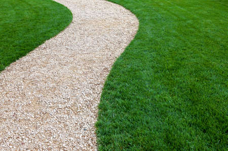garden lawn: Curved garden path with fresh green cultivated lawn Stock Photo