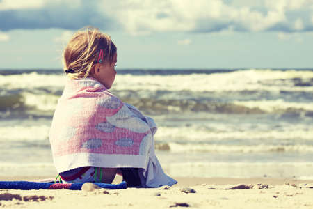 lonely: Lonelly little girl sitting on the beach covered with towel and looking at the sea Stock Photo