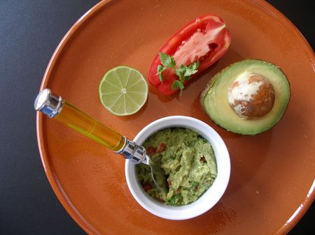 guacamole: Guacamole presented with tomato on an earthware plate