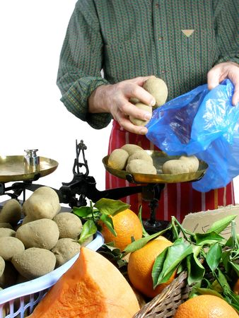 weighting: Vendor is selling potatoes for a customer at the market Stock Photo