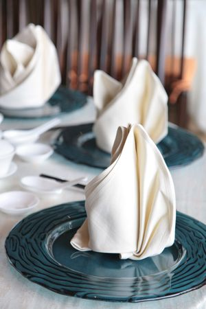 serviettes: Fine dining Chinese cuisine table setting with glass plates and cotton fabric serviettes