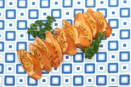 fillers: Garlic bread slices laid on a retro blue squared table-mat