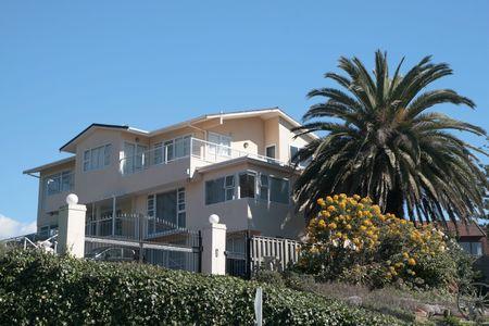 nags: Una casa beachside en �rbol de la sol y de palma en el jard�n Foto de archivo