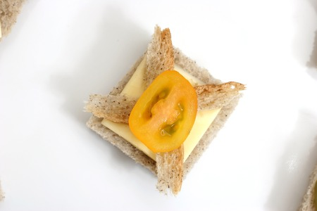 Yellow cherry tomato with a slice of cheese canap�, top view photo