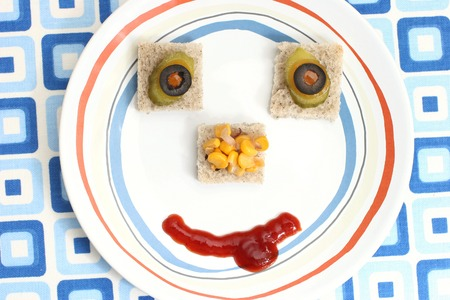 Fruit and vegetable canap�s arranged as a face on a small plate photo