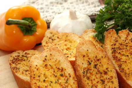 Toasted garlic bread on a wooden tray with yellow capsicum, garlic and parsley. photo