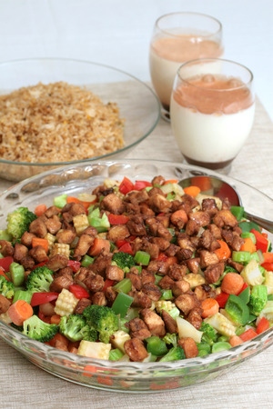 Mixed vegetable and meat dish with egg fried rice and milk drinks in background photo