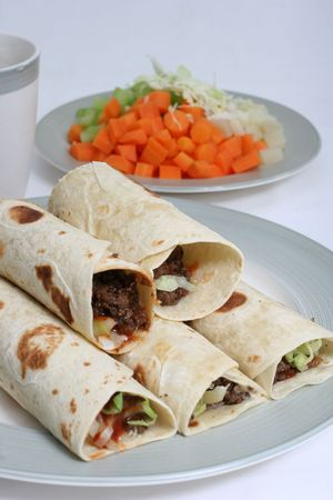 mincing: Minced beef rolled in pita bread with a serving of fresh vegetables.
