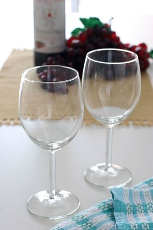 an ounce: Empty wine glasses with bottle of wine and some grapes in the background Stock Photo