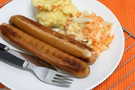 chunky: Pan grilled jumbo frankfurters with side serving of mash and coleslaw Stock Photo