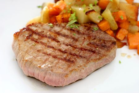 A round eye steak fried on a grilling pan with a serving of mixed cubed vegetables  Stock Photo - 1930202