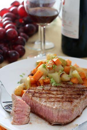 carnes y verduras: Una ronda de ojos bistec frito en una sart�n la parrilla con una raci�n de verduras mixtas cubed