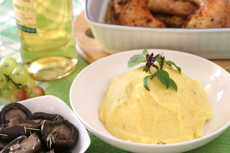 heaped: Mashed potato with basil heaped up and smoothed off in a white ceramic bowl Stock Photo