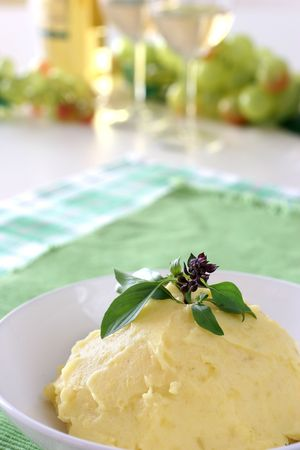 heaped: Mash potato with basil heaped up and smoothed off in a white ceramic bowl