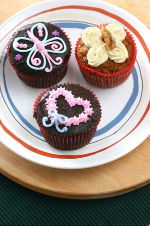 Fancy carrot and chocolate cupcakes with icing design on top photo