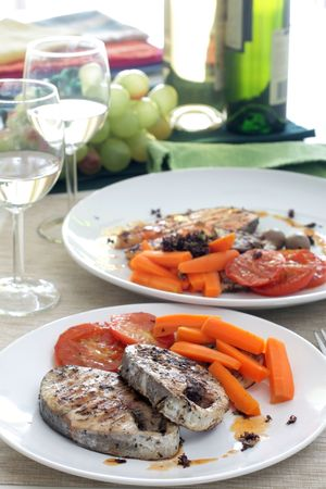seared: Pan seared mackerel served with carrots, sliced tomatoes and white wine Stock Photo