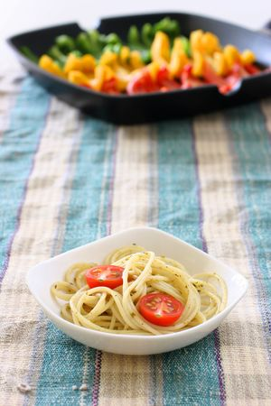 olio: Pasta olio with halved cherry tomato in small square shaped bowl on