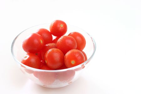 intense flavor: Cherry tomatoes in a transparent glass bowl on a white table-top Stock Photo