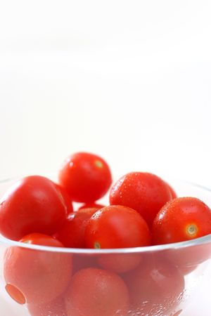 Cherry tomatoes in a transparent glass bowl on a white table-top Stock Photo