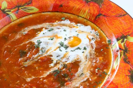 Homemade chunky tomato soup with chopped basil and garlic and a dash of olive oil photo