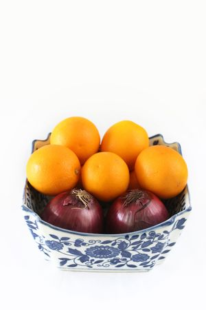 cowl: Organic onions and oranges in a square, ornate china cowl Stock Photo