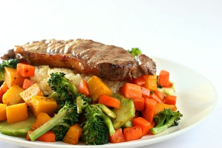 cubed: Beef steak on garlic and ginger flavored rice surrounded by mixed vegetables Stock Photo
