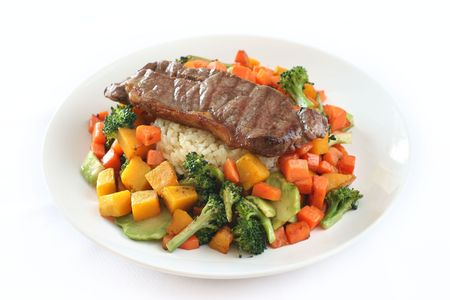 roughage: Beef steak on garlic and ginger flavored rice surrounded by mixed vegetables Stock Photo