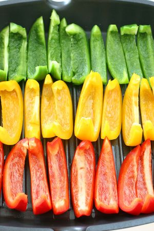 arranged: Colorful rows of green, yellow and red capsicum strips prepared for cooking on a pan Stock Photo