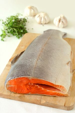 thawed: Large slab of tail portion of fresh Atlantic salmon on wooden chopping board