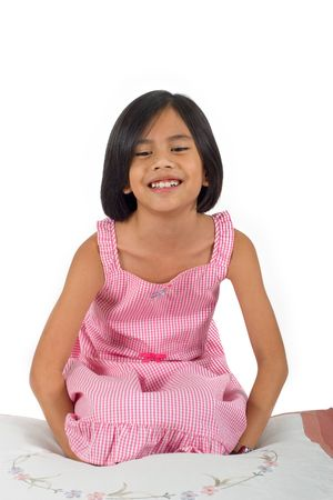 Young pretty Eurasian Chinese girl in pink dress seated on floor smiling photo