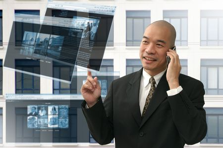 Oriental looking bald business man on phone and internet photo