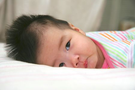 Chinese baby lying in bed photo