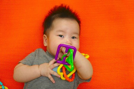 Five month old placing toy in mouth photo