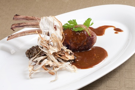 Seared, grilled rib of lamb with black lentils and gravy photo
