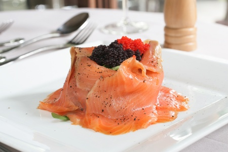 upscale: Salmon volcano salad with rocket, topped with red and black caviar Stock Photo