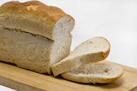 A fresh cut loaf on a wooden board Stock Photo