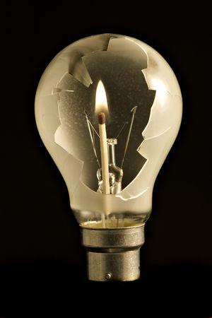 A broken light bulb with a burning match inside