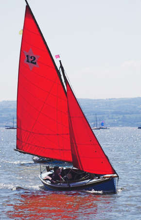 The leader in a yacht race skims across the sea Stock Photo