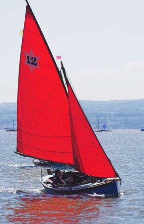 across: The leader in a yacht race skims across the sea Stock Photo