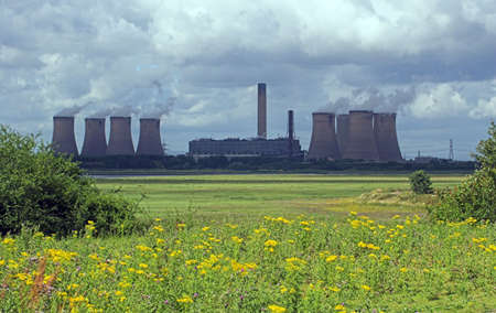A view across fields of wildflowers to a coal powered power station belching out steam, under a cloudy sky. Fiddlers Ferry power station, UK