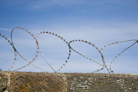 forbids: Barbed wire on top of a wall forbids entry Stock Photo