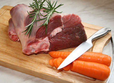 A joint of lamb ready for cooking,with carrots and rosemary
